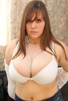 Cindy Milley untying her top to show the cleavage of her big breasts in H-cup bra photos from CindyMilley.com