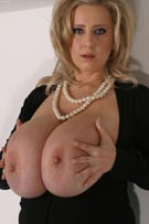 Nelli Roono pops her massive mammaries out of her sexy black dress at Busty.pl