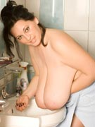 Bianca Bloom topless in a towel putting on makeup and oiling her boobs at Big Tits Glamour - BigTitsGlamour.com