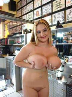 Busty blonde girl in the tattoo shop at BigTitsRoundAsses